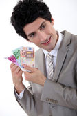 Businessman holding Euro bank notes — Stock Photo
