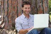 Smiling man using laptop — Stock fotografie