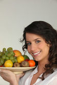 Woman holding a bowl of fruit — Stock Photo