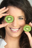 Woman covering eye with kiwi — Stock Photo