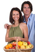 Man and woman with a basket of fruit — Stock Photo