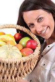 Woman holding fruit basket — Stock Photo