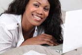 African woman lying and having fun with her laptop — Stock Photo