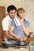 Young woman on the phone while cooking dinner — Stock Photo