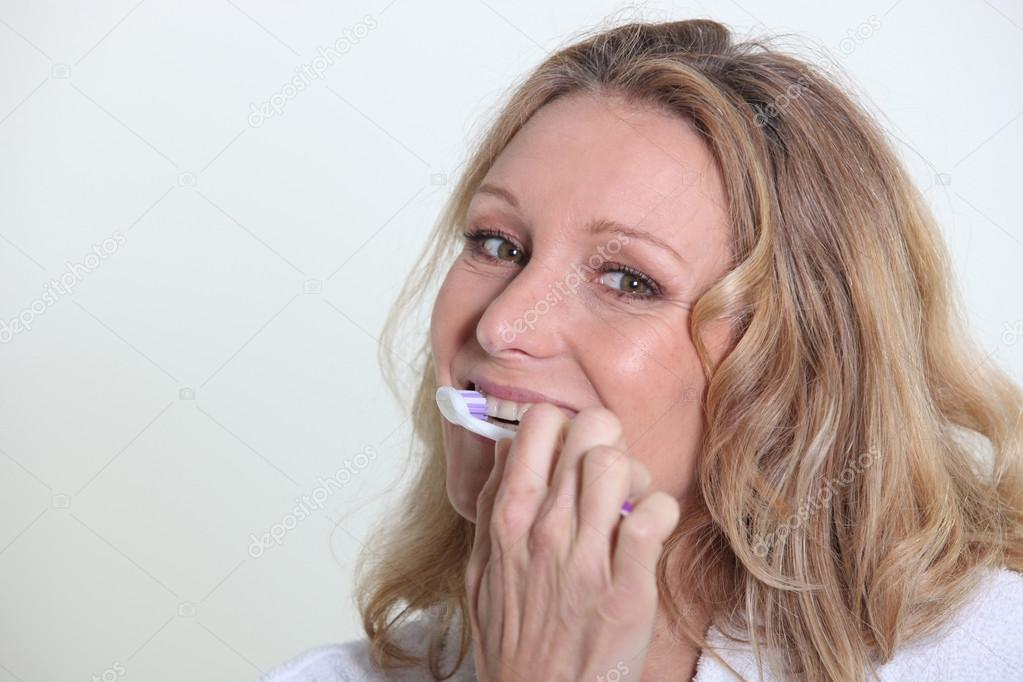 Blond woman smiling whilst brushing teeth  Stock Photo #14100774
