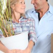 Couple smiling with plant — Stock Photo #14111021