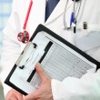 Stock Photo: Doctor holding clipboard with patients results