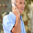 Senior citizen making a call outdoors — Stock Photo #14138053