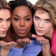 Three female friends blowing kisses — Stock Photo