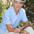 Senior man wearing a hat whilst in the garden — Stock Photo #14138183