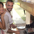 Couple cooking food on outdoor barbecue — Stock Photo #14138334