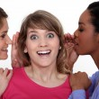 图库照片: Two women whispering into friends ear
