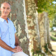 Senior man standing by a row of trees — Stock Photo #14138403