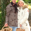 Middle-aged couple with basket of mushrooms — Stock Photo #14138424