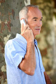 Senior citizen making a call outdoors — Stock Photo