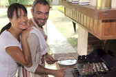 Couple cooking food on outdoor barbecue — Stock Photo