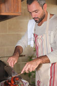 Man in kitchen roasting meat and merguez sausages — Stock Photo