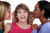 Two women whispering into friends ear — 图库照片