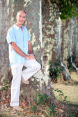 Grey-haired man leaning against tree — Stock Photo