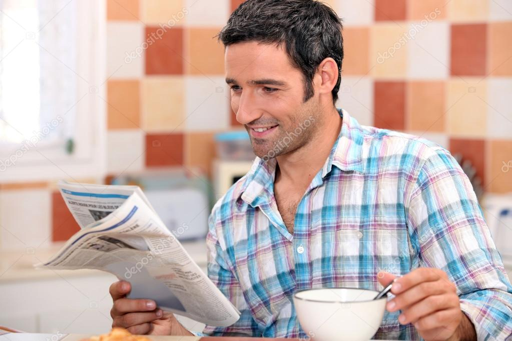 Black man having breakfast with newspaper — Stock Photo #14138325