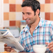 Royalty-Free Stock Photo: Black man having breakfast with newspaper