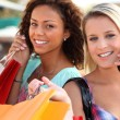 Two woman on mobile phones holding shopping bags — Stock Photo