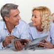 Married couple reading magazine — Stockfoto #14142308