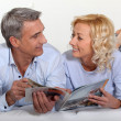 Married couple reading magazine — Foto de stock #14142308