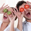 Covering his eyes with a couple slices of kiwi and tomato — Stock Photo #14142532