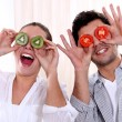 Couple holding fruit to their eyes — Stock Photo