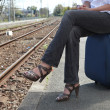 Woman seated on suitcase waiting for train on platform Delaire_Constance_15 - Stock Photo