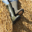 A farmer seated on a straw bale, close-up of his legs — Stock Photo #14148583