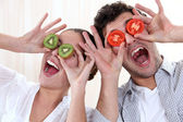 Covering his eyes with a couple slices of kiwi and tomato — Stock Photo