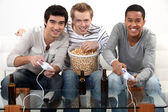 Three friends playing video games while drinking beer. — Stock Photo