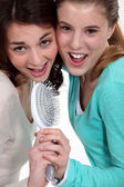 Two teenagers singing with a brush. — Stock Photo