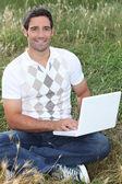 Man sat in field using laptop computer — Stock Photo