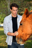 Young man caressing a horse — Stok fotoğraf