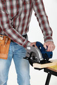 Craftsman with chainsaw cutting wood — Stock Photo