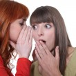 Foto Stock: Womwhispering to her friend