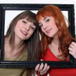 Women holding wooden frame - Stock Photo