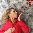 Woman in red lying on a rug and blowing rose petals — Stock Photo