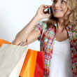 Blond woman holding shopping bags talking on cellphone — Stock Photo
