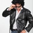 Royalty-Free Stock Photo: Man in a silly black wig and biker jacket