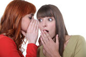 Woman whispering to her friend — Stock Photo