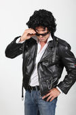 Man in a silly black wig and biker jacket — Stock Photo