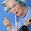 Senior woman with curlers in her hair cooking — Stock Photo #14170536