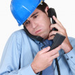 Overwhelmed engineer answering ringing phones - Stock Photo