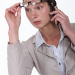 Shocked woman lifting glasses during call — Stock Photo