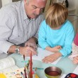 Grandfather with grandson drawing — Stock Photo #14173296