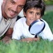 Stock Photo: Father and son examining grass with magnifying glass